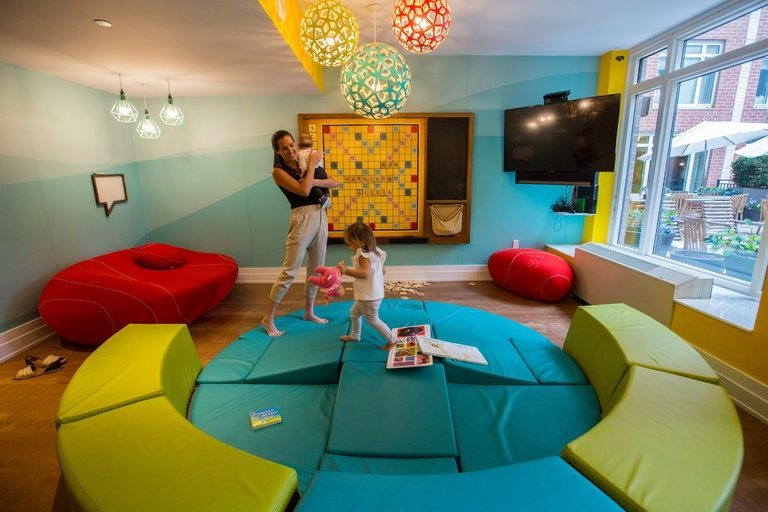 Talli Levine, 30, with her daughter Olivia, 1, and son, Harrison, in the playroom at the Brompton on the Upper East Side. Credit Hiroko Masuike/The New York Times